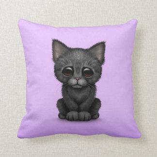 Gato negro lindo triste del gatito en púrpura almohada