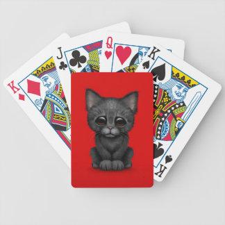 Gato negro lindo triste del gatito en rojo barajas de cartas