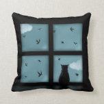 Gato negro que considera hacia fuera la ventana el almohadas