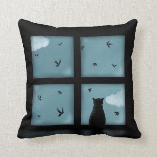 Gato negro que considera hacia fuera la ventana el cojines
