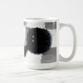Gato negro que mira para arriba taza de café