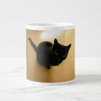 Gato negro que se sienta en un suelo de parqué taza grande