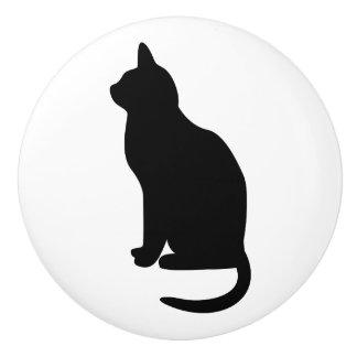 Gato negro que se sienta que hace frente a la pomo de cerámica