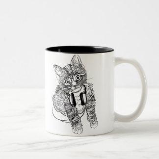 Gato negro y blanco divertido en el ejemplo de los taza de café de dos colores
