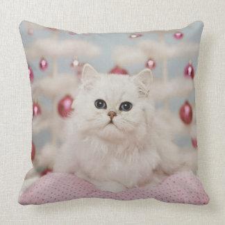 Gato persa que se sienta en la almohada rosada