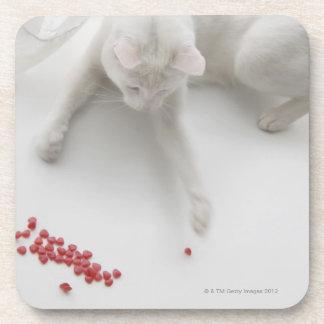 Gato que juega con el caramelo en forma de corazón posavasos