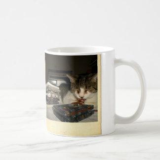 Gato que mastica la cinta de casete taza de café