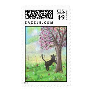 Gato que rasguña sellos del árbol