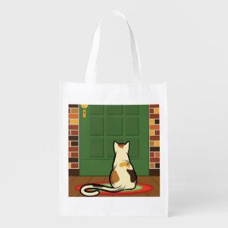 Gato que se sienta delante del paso de la puerta bolsa reutilizable