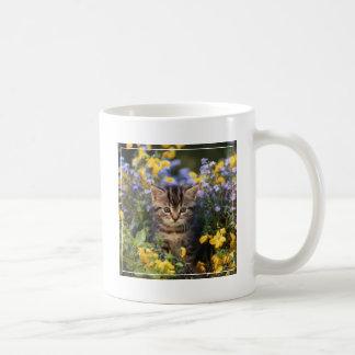 Gato que se sienta en jardín de flores taza