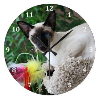 Gato siamés hermoso que juega con el juguete reloj redondo grande