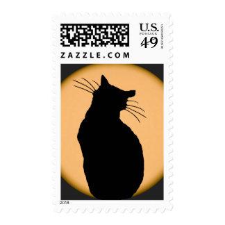 Gato silueteado contra el sello de la luna
