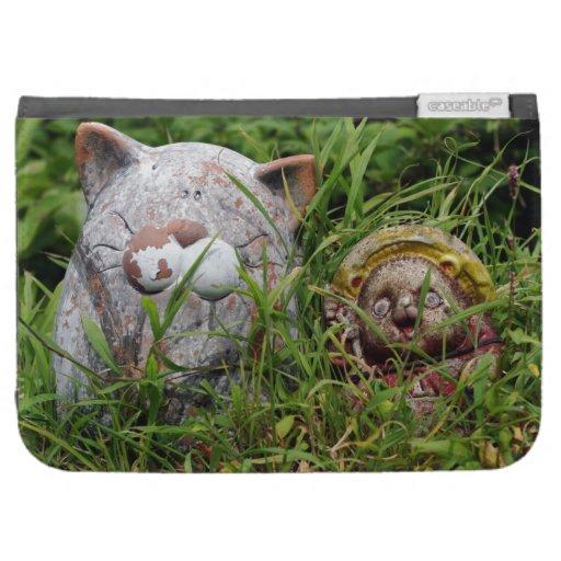 Gato y estatuas lindos de Tanuki en la hierba