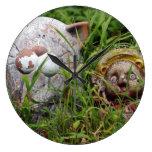 Gato y estatuas lindos de Tanuki en la hierba Reloj De Pared