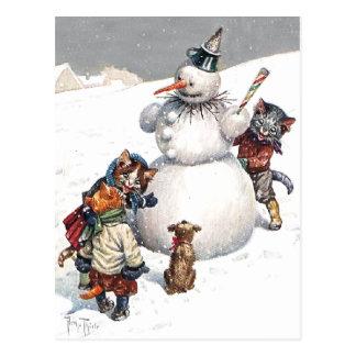 Gatos adorables que construyen un muñeco de nieve postal