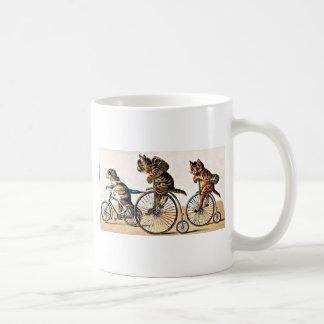 Gatos y perro del vintage en una bici taza de café