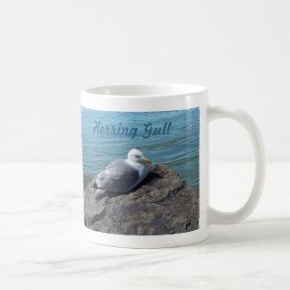 Gaviota de arenques que descansa sobre el embarcad tazas de café