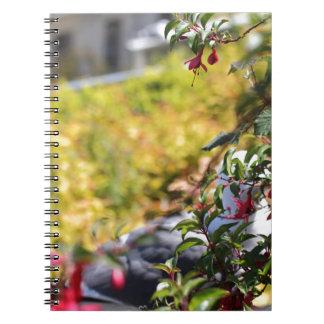 Gaviota detrás de un campo de flores spiral notebooks