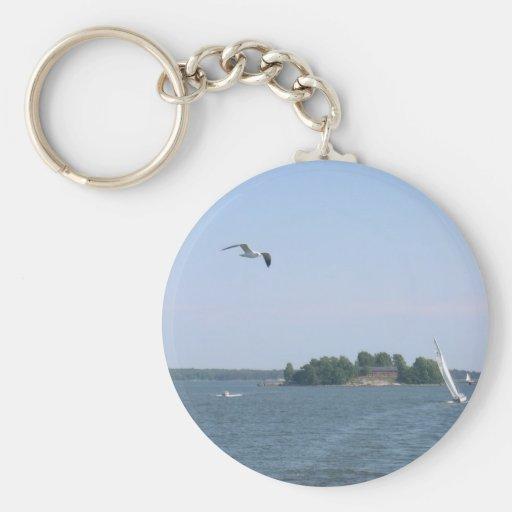 Gaviota que vuela cerca de la isla y del yate en H Llavero Redondo Tipo Pin
