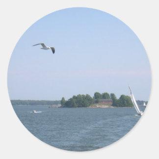 Gaviota que vuela cerca de la isla y del yate en etiquetas redondas