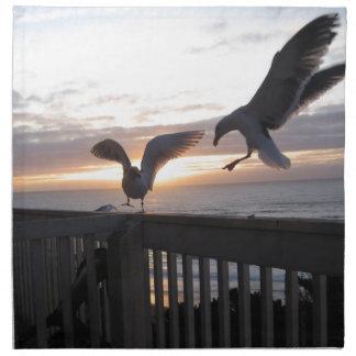Gaviotas en la cubierta en la puesta del sol servilletas de papel