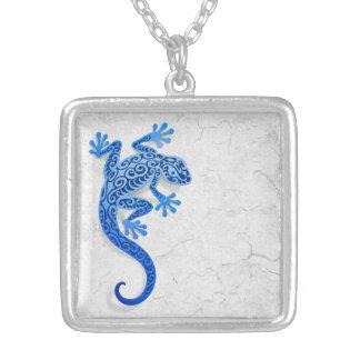 Gecko azul que sube en una pared blanca joyeria personalizada