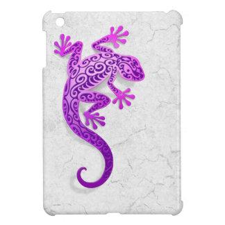 Gecko púrpura que sube en una pared blanca
