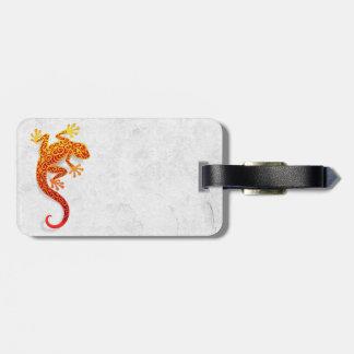 Gecko rojo que sube en una pared blanca etiquetas maletas