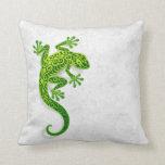 Gecko verde que sube en una pared blanca almohadas