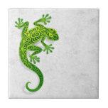 Gecko verde que sube en una pared blanca azulejos cerámicos