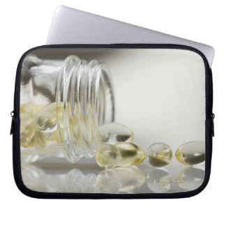 Gelcaps spilling out of glass bottle computer sleeves