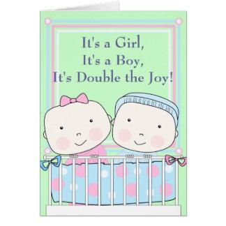 Gemelos en bebé del pesebre, del chica y del tarjeta de felicitación