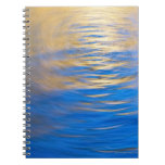 Gently rippled water reflecting gold and blue spiral notebook