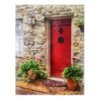 Geranios por la puerta roja tarjeta postal
