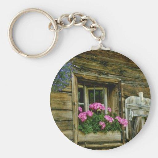 Geranios rosados en flores de la ventana llaveros