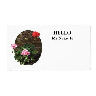 Geranios rosados y rojos contra ladrillo etiqueta de envío