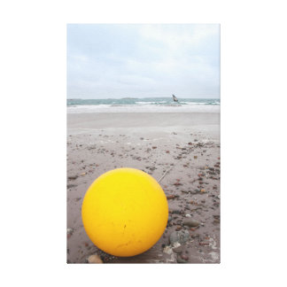 giant yellow buoy on beach canvas print