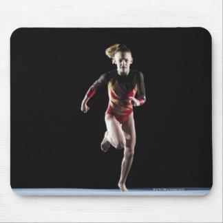 Gimnasta (12-13) que corre en la estera mouse pad