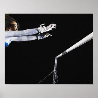 Gimnasta (9-10) que alcanza para las barras desigu posters