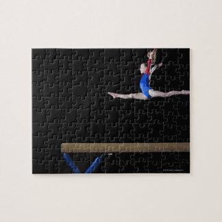 Gimnasta (9-10) que salta en el haz de balanza 2 puzzles con fotos