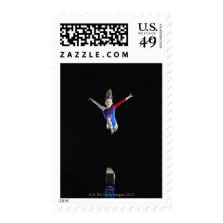Gimnasta (9-10) que salta en haz de balanza sello