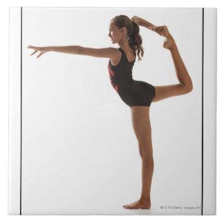 Gimnasta de sexo femenino (12-13) que equilibra en azulejo ceramica