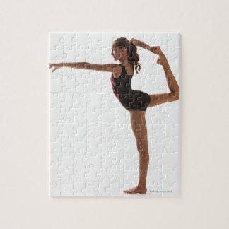 Gimnasta de sexo femenino (12-13) que equilibra en rompecabezas con fotos