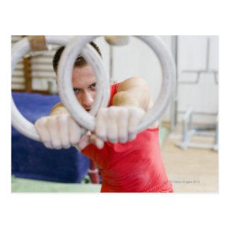 Gimnasta de sexo masculino en los anillos postales