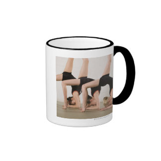 Gimnastas que presentan upside-down taza a dos colores