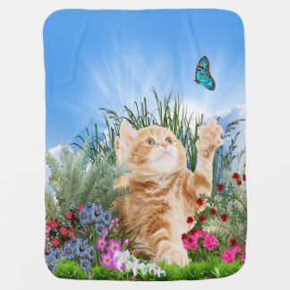 Ginger kitten playing with a butterfly receiving blanket