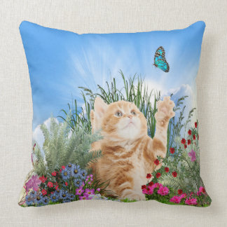 Ginger kitten playing with a butterfly throw pillow