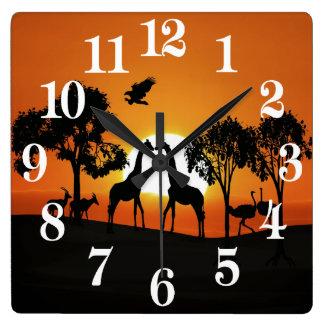 Giraffe at sunset square wall clock