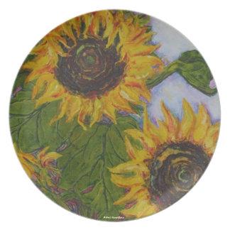 Girasol amarillo en la placa azul del fondo platos