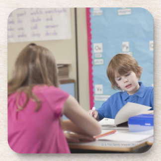 Girl (10-11) and boy (6-7) reading in classroom beverage coaster